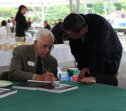 "Sam Austin, Laboratory Director Emeritus, (seated) signs a copy of his book, ""Up From Nothing: The Michigan State University Cyclotron Laboratory."""