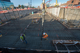 Workers place concrete for the lid of the linear accelerator tunnel.