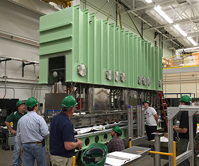 FRIB Cryomodule Department employees test fit the vacuum vessel on the first production cryomodule.
