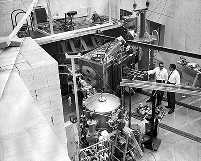 This photo shows the initial setup of the experimental area for the K50 cyclotron. The cyclotron itself is at the rear of the picture and the beamline and the second-hand Rochester scattering chamber are at the front.