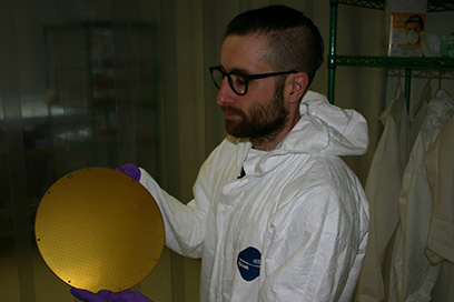 Yassid Ayyad, detector systems physicist at the National Superconducting Cyclotron Laboratory at Michigan State University, is part of the research team that observed a rare decay in the exotic beryllium-11 nucleus. Here he holds the pad plane of the Active Target Time Projection Chamber detector that was used in the experiment. Credit: National Superconducting Cyclotron Laboratory