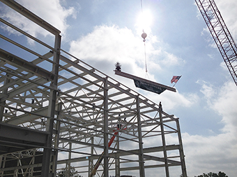 The final beam is put in place, signifying completion of the steel structure that will soon become the SRF Highbay