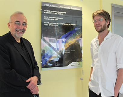 Witek Nazarewicz (FRIB Chief Scientist) and Léo Neufcourt (Research Associate) shake hands in front of an FRIB poster.