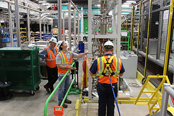 Three FRIB employees lower the vertical beamline into the front end of the facility.