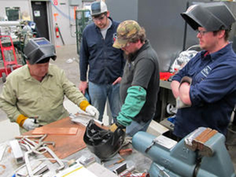 Joseph Brock from JLab demonstrates titanium welding techniques while Ian Sprague, Jason VanAken, and Jim Brownlee observe.